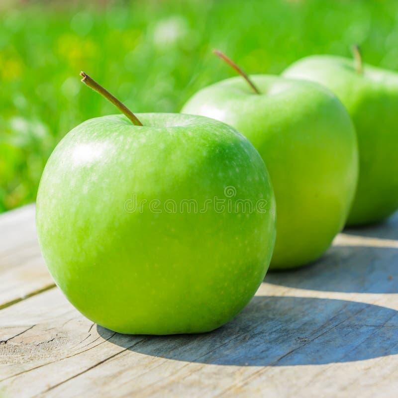 Nytt kantjusterat geen äpplen på trätabellen över grenngräsbakgrund arkivbild