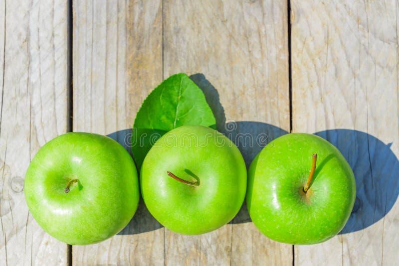 Nytt kantjusterat geen äpplen på trätabellen, bästa sikt arkivbild