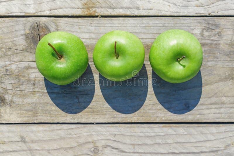 Nytt kantjusterat geen äpplen på trätabellen, bästa sikt royaltyfria bilder