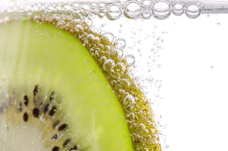 Nytt Kiwi Slice In Cold Carbonate vatten arkivfoton