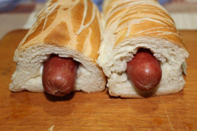 Nytt lagad mat varmkorv i färgrika brödpinnar på en träyttersida royaltyfri fotografi