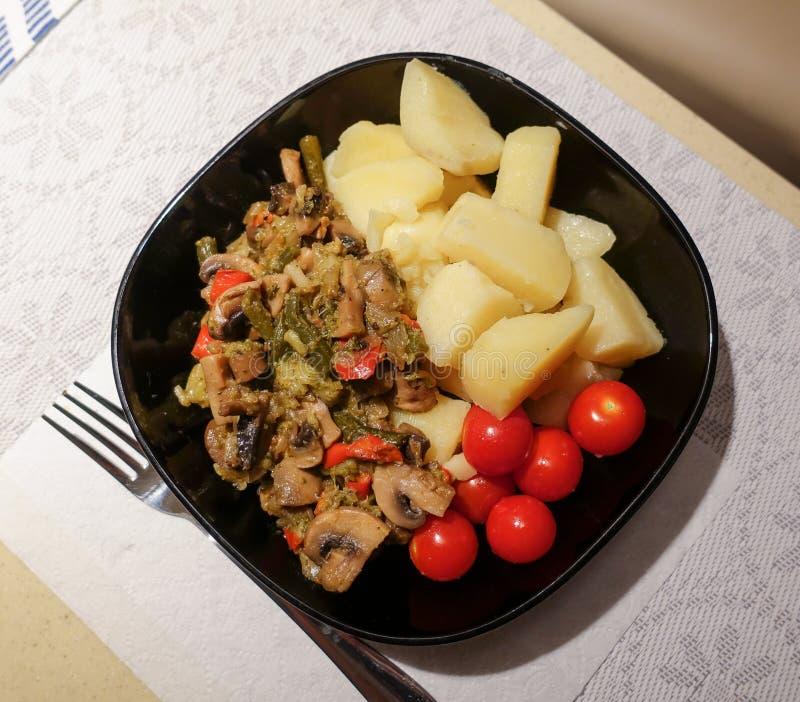 Nytt lagade mat kokta potatisar med champinjoner och k?rsb?rsr?da tomater N?rbild Vegetarisk mat Diet-n?ring royaltyfria bilder