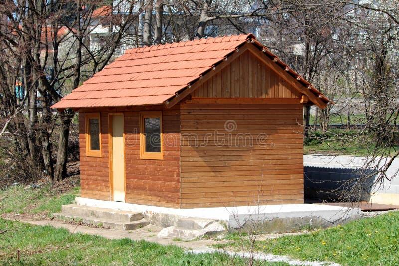 Nytt litet trähus med den enkla ingångsdörren och två fönster som monteras på det konkret och stenfundamentet som omges med oklip royaltyfri fotografi