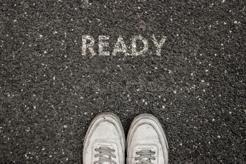 Nytt livbegrepp, Motivational slogan med ordet som ÄR KLART på jordningen av asfalt arkivbilder