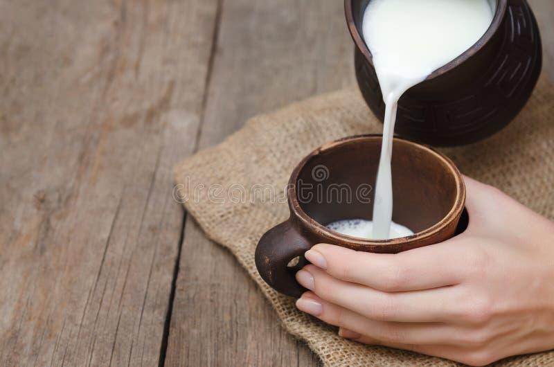Nytt mjölka att hälla i ett leralock fotografering för bildbyråer