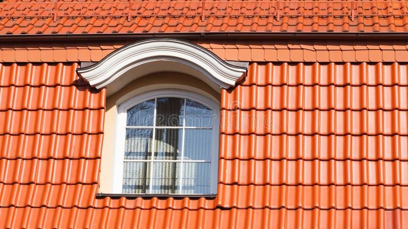 Nytt modernt tak som göras av röda keramiska tegelplattor, och ett stort loftfönster royaltyfri foto