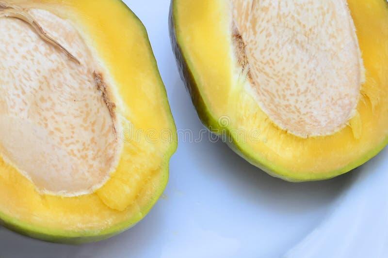 Nytt moget mangosnitt i halva Abstrakt bakgrund med fragment av klippt frukt Begrepp: sund mat arkivfoto