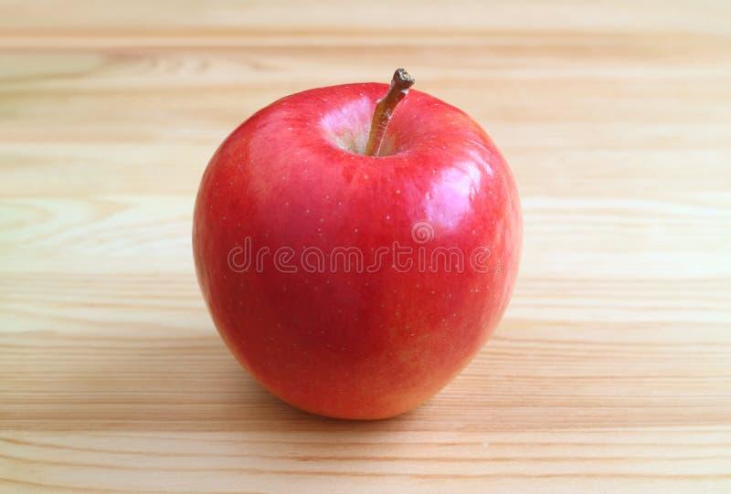 Nytt moget rött äpple som isoleras på ljust - brun trätabell fotografering för bildbyråer