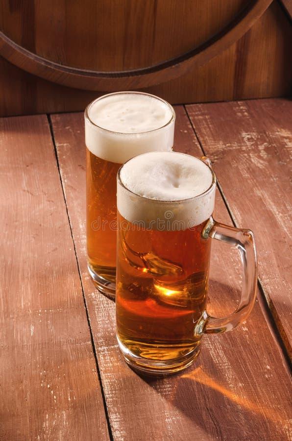Nytt och kallt öl i exponeringsglas Smakligt ölbegrepp på träbackg arkivbild