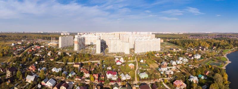 Nytt område med höghus i den nya Moskva på bakgrunden av låghus- privat sektorhus royaltyfria foton