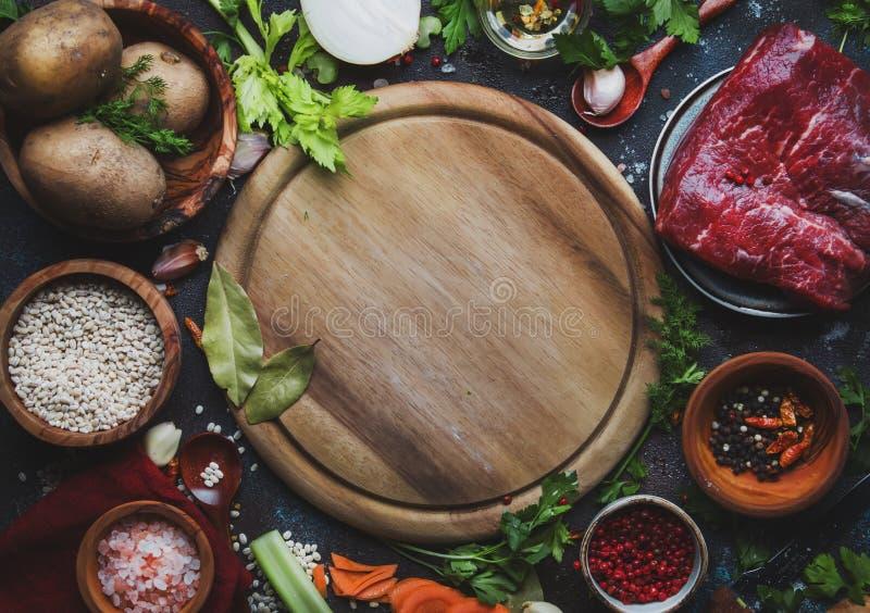Nytt organiskt grönsaker, ingredienser, kryddor och kött för soppa eller buljong på tappningköksbordbakgrund med lantligt trä royaltyfri fotografi