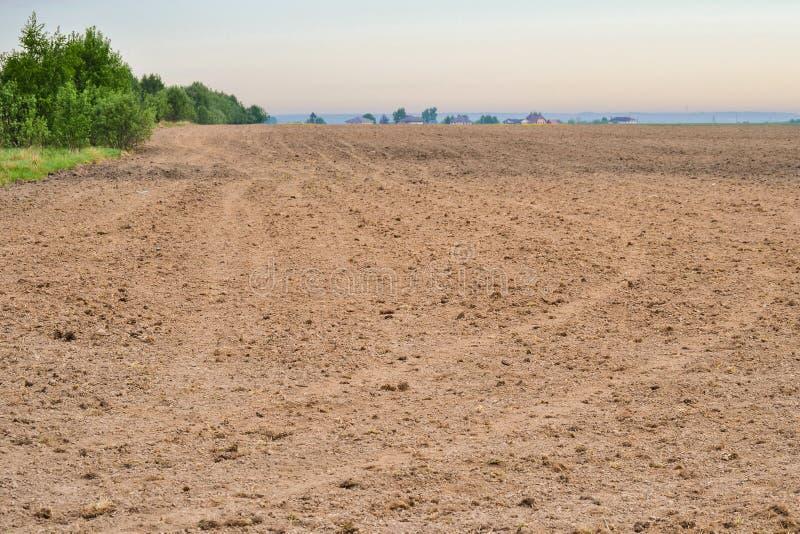 Nytt plogat fält i våren som är klar för odling Fjädra landskapet i bygden med fält mot himlen Jordbruk royaltyfria bilder