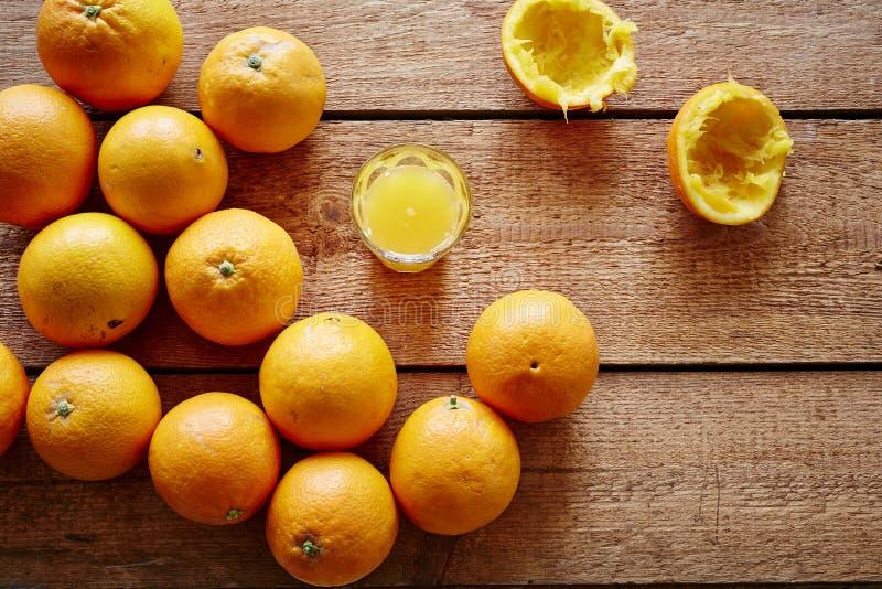 Nytt pressande orange fruktsaft och grupp av apelsiner royaltyfri bild