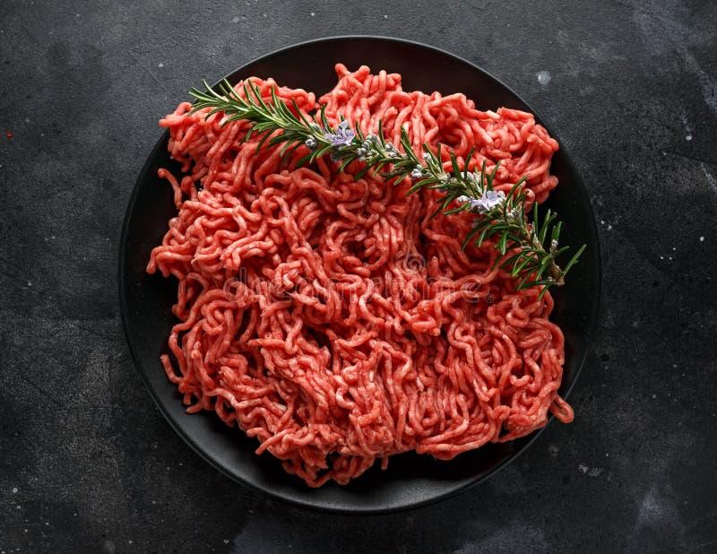 Nytt rått finhackar, finhackat nötkött, jordkött med örter och kryddor på den svarta plattan royaltyfri bild