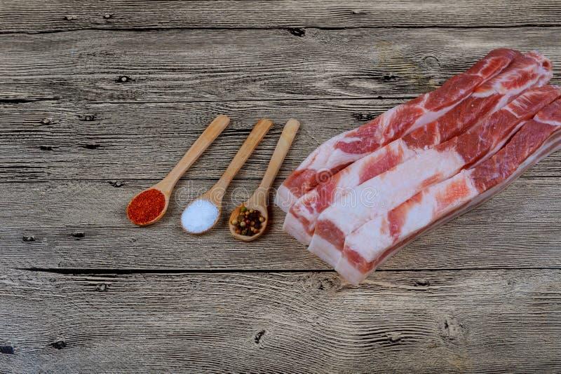 Nytt rått griskött späcker med kryddor för att grava på ett bitande träbräde royaltyfri fotografi