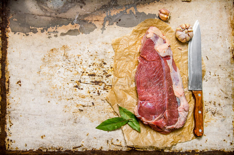 Nytt rått kött med en stor kniv och en lagerblad royaltyfri foto