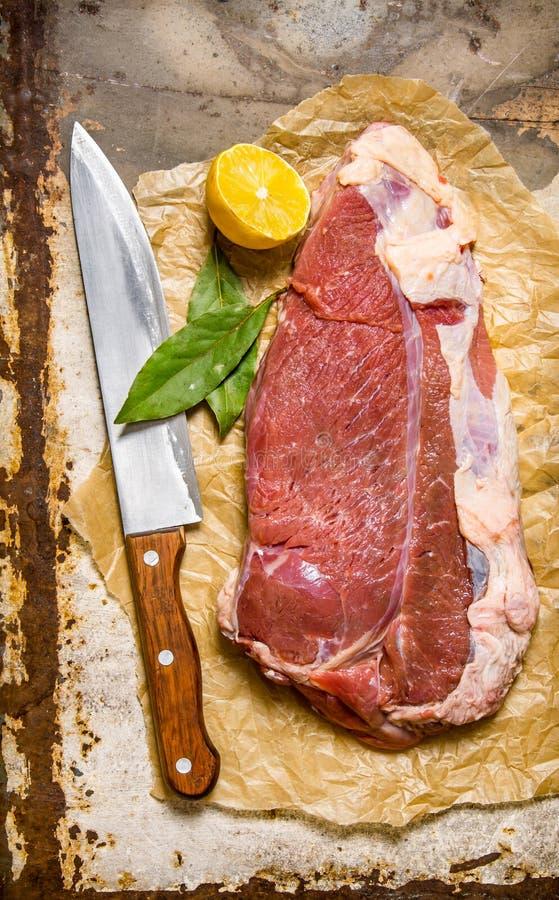 Nytt rått kött med en stor kniv och en lagerblad royaltyfria bilder