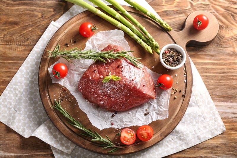 Nytt rått kött med kryddor, örter och grönsaker på träbräde royaltyfria foton