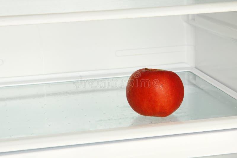Nytt rött äpple i inhemskt kylskåp royaltyfria foton