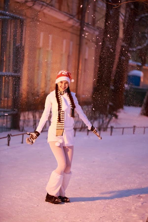 nytt s år för helgdagsafton Flickan i ett vitt klänninganseende under att snöa royaltyfria bilder