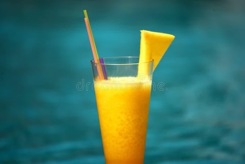 Nytt sammanpressad orange fruktsaft för fruktananas på en bakgrund av havet royaltyfri fotografi