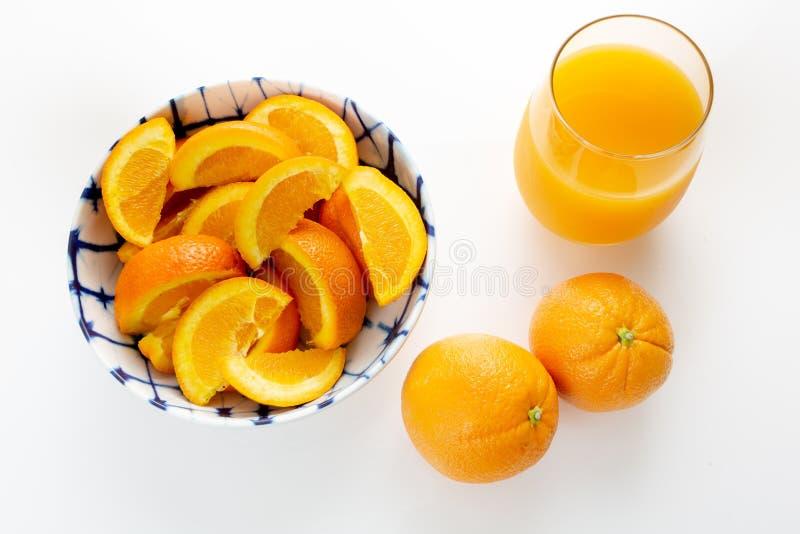 Nytt sammanpressad orange fruktsaft i ett exponeringsglas bredvid en bunke av apelsinskivor och två apelsiner som väljs precis av arkivfoto