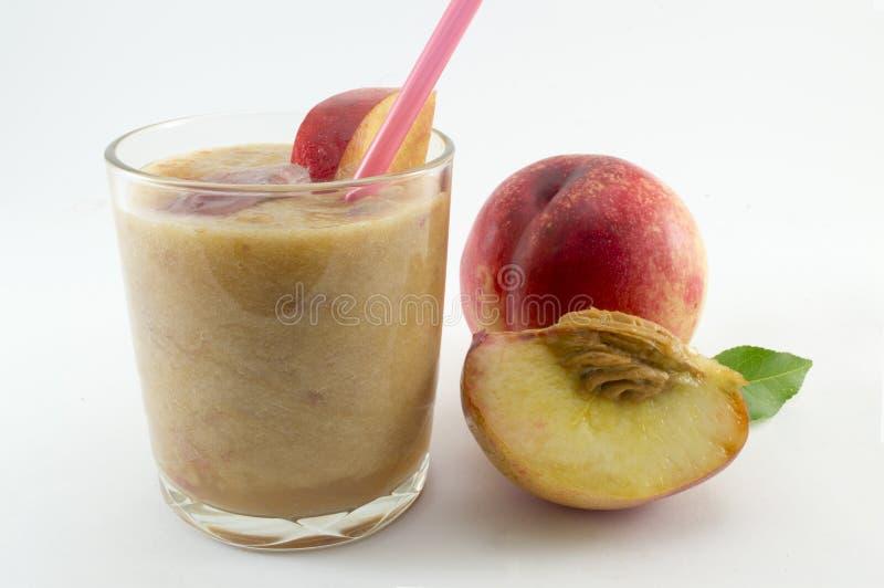 Nytt sammanpressad persikafruktsaft och nya persikor på vit royaltyfria bilder