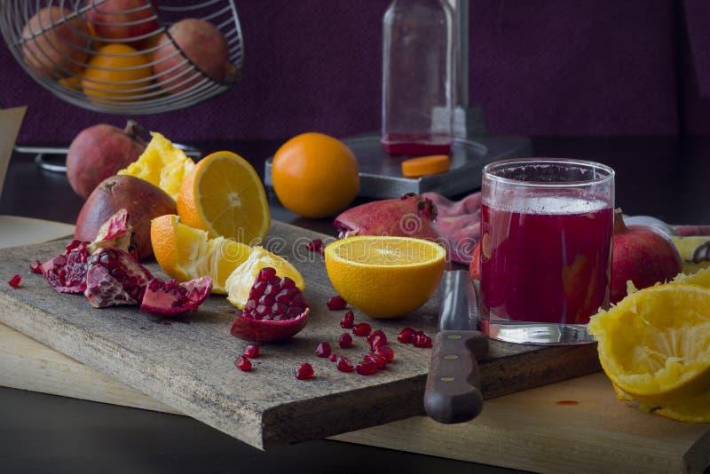 Nytt sammanpressat med hjälpen av en mekanisk press, fruktsaften av granatäpplet och apelsinen arkivfoton