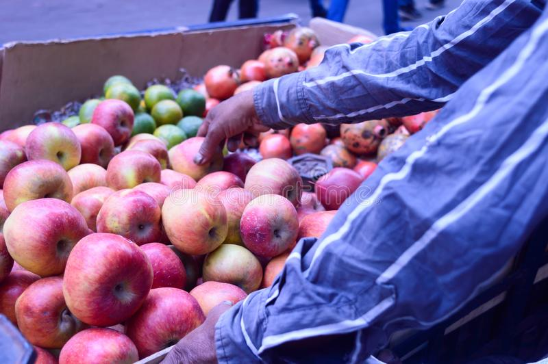 Nytt shoppar den saftiga valda högen av röda äpplen som visas för kund i en detaljhandel, nära vägrenen, Kolkata, Indien royaltyfri foto