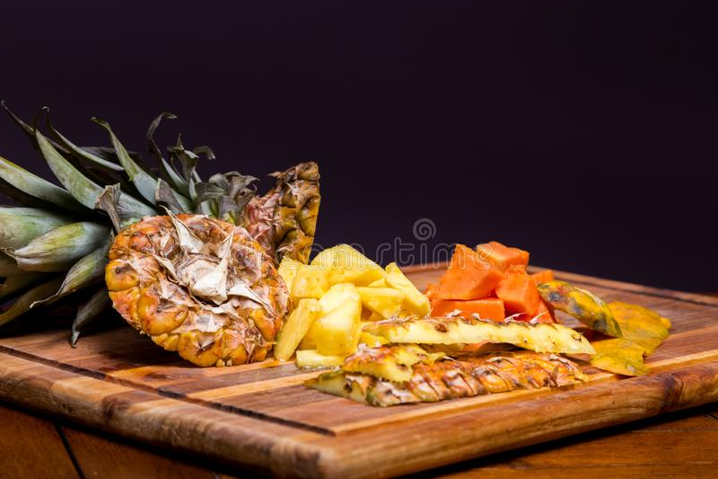 Nytt snittananas och papaya på en träskärbräda arkivfoto