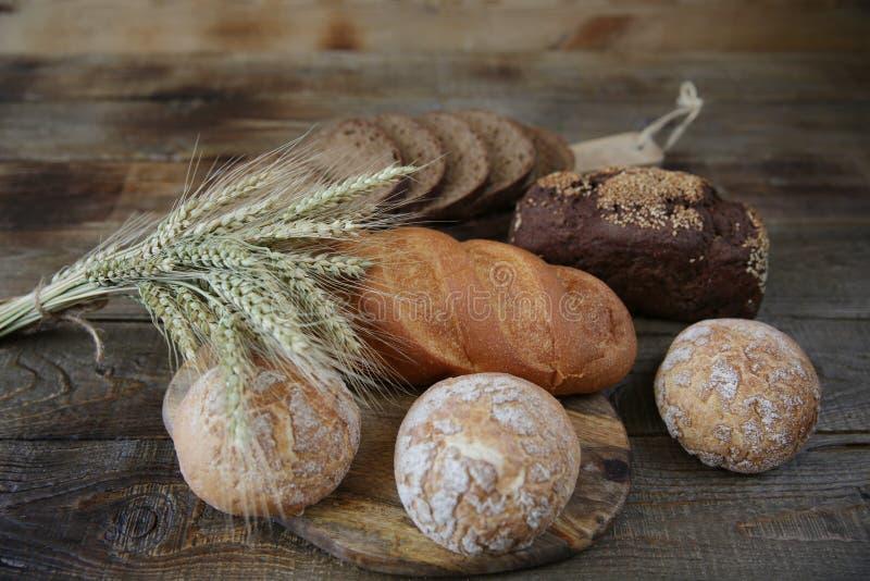 Nytt varmt bröd för råg och för vete med öron, närbild på en trälantlig bakgrund royaltyfri fotografi