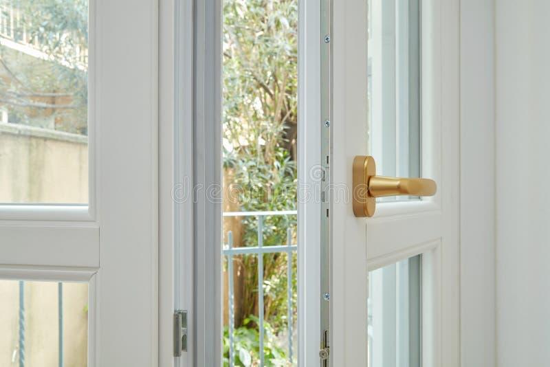 Nytt vitt dubbelt glasat öppet fönster med det guld- handtaget arkivbild