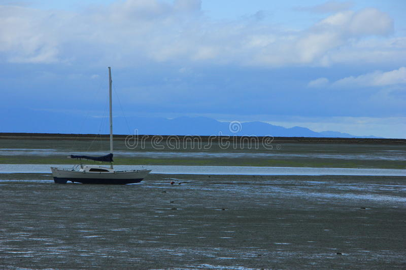 NZ, South Island, Lonely boat on the Beach during Low tide royalty free stock images