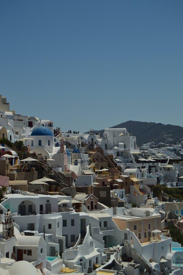 Oändlig backe mycket av typiska vit- och blåtthus i den härliga staden av Oia på ön av Santorini Arkitektur LAN arkivbild