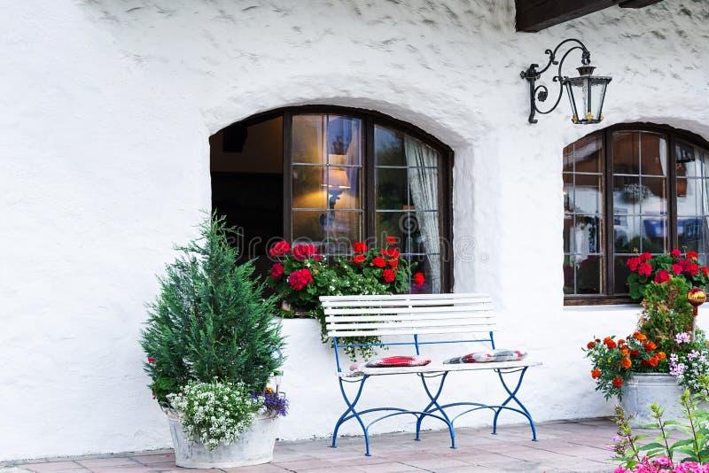 Ościenny terytorium dekoruje z białą ławką, kwiatami i fałszującym lampionem, zdjęcia stock