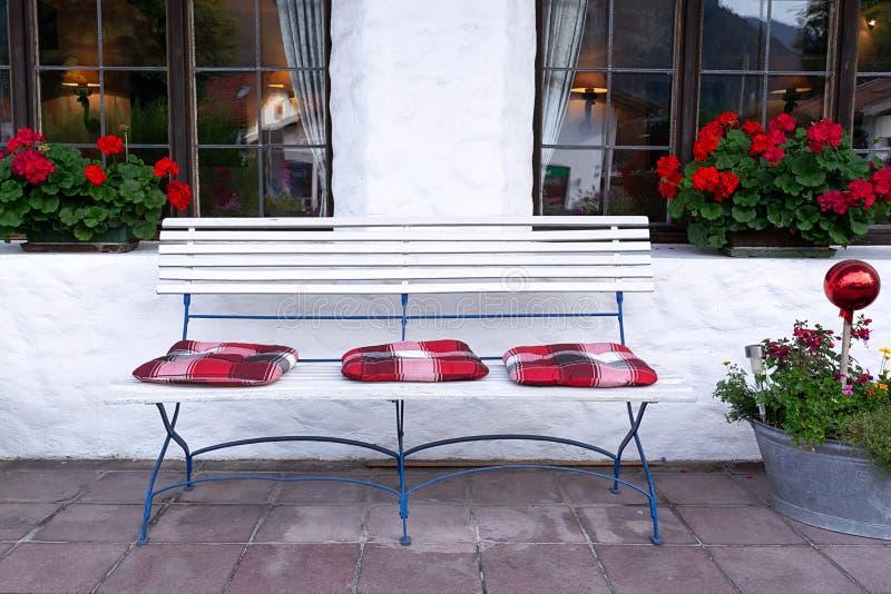 Ościenny terytorium dekoruje z białą ławką, kwiatami i jaskrawymi poduszkami, zdjęcie stock