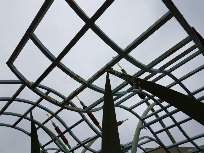 Ośniedziała wyginająca się metal struktura, chmury w niebie i fotografia stock