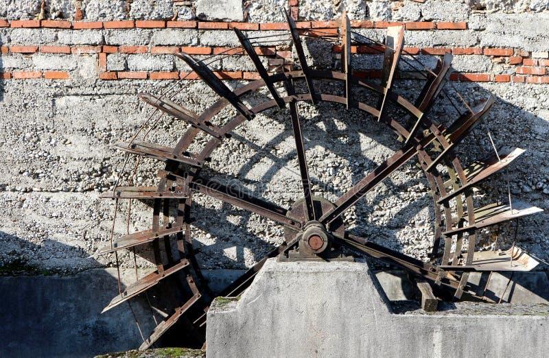 Ośniedziały wielki stary koło na betonowej ścianie zaniechany wodny młyn zdjęcia royalty free