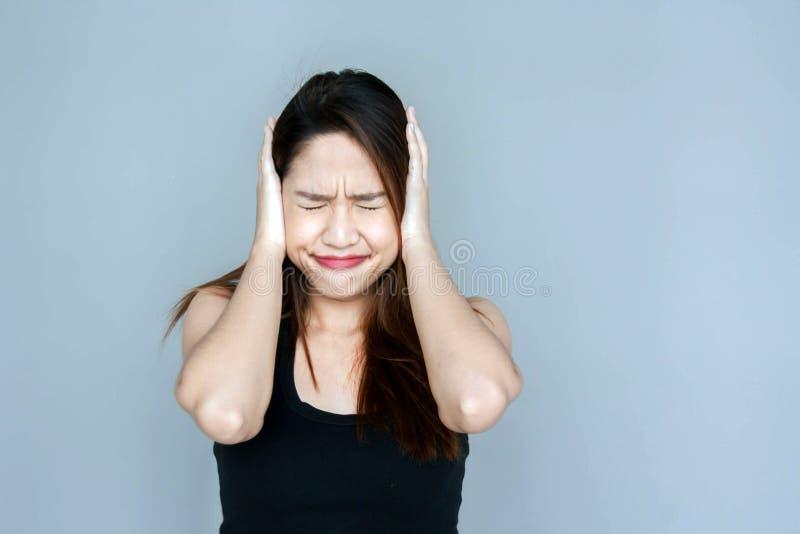 Oído tailandés del cierre de la mano de la señora a muy foto de archivo libre de regalías