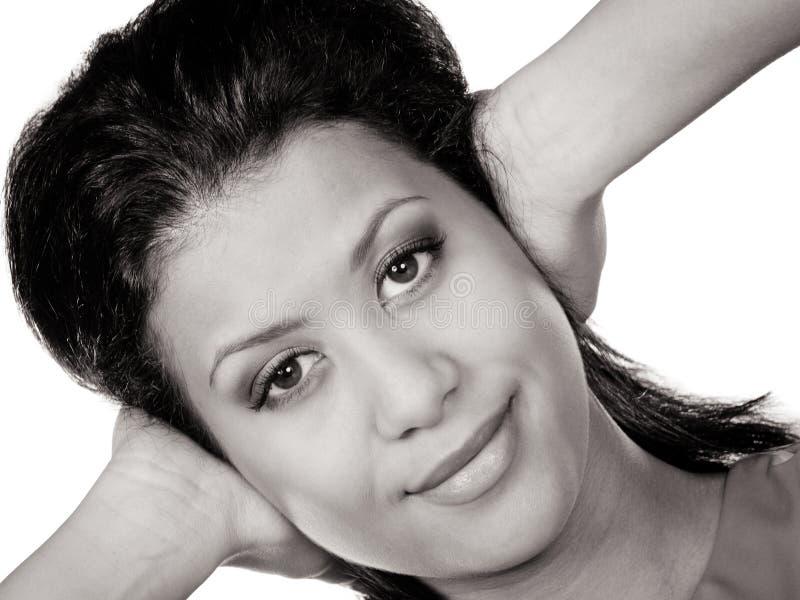 Oídos cerrados de la mujer de la raza mixta con las manos imagen de archivo