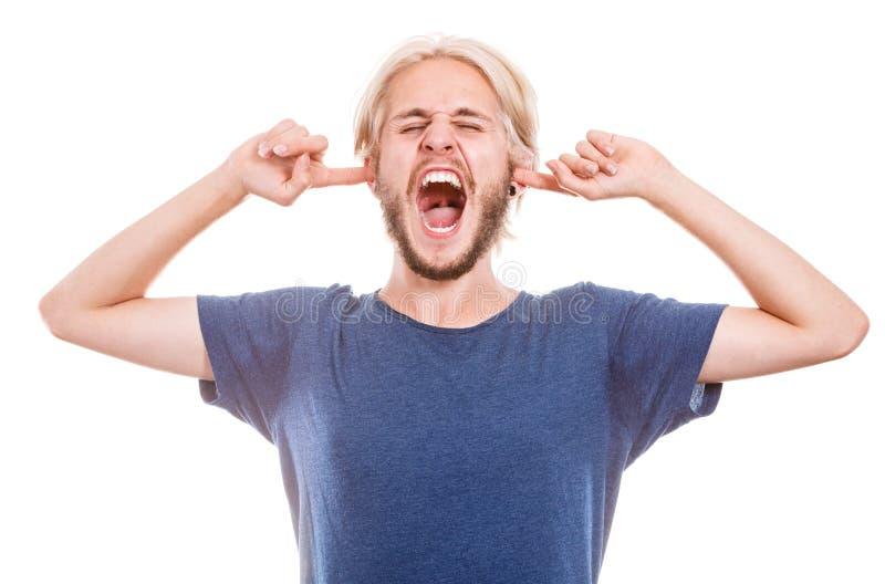 Oídos cerrados del hombre enojado con los fingeres imagen de archivo libre de regalías
