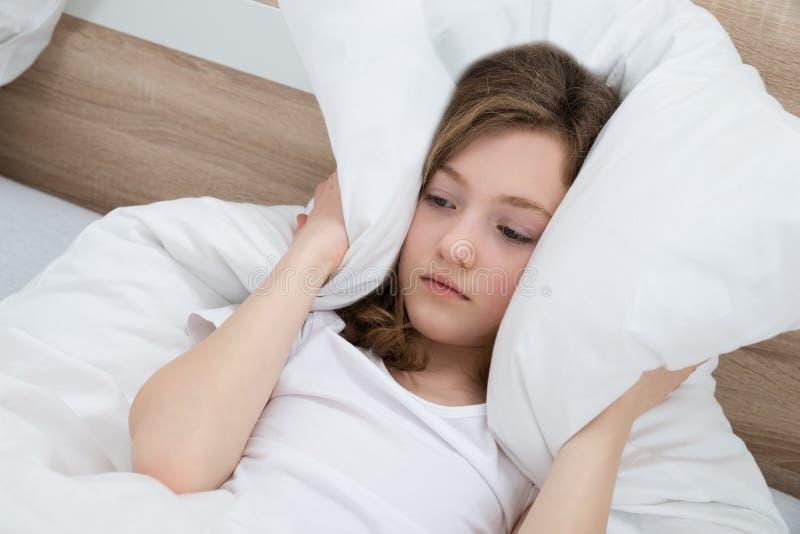 Oídos de la cubierta de la muchacha con la almohada imagen de archivo libre de regalías