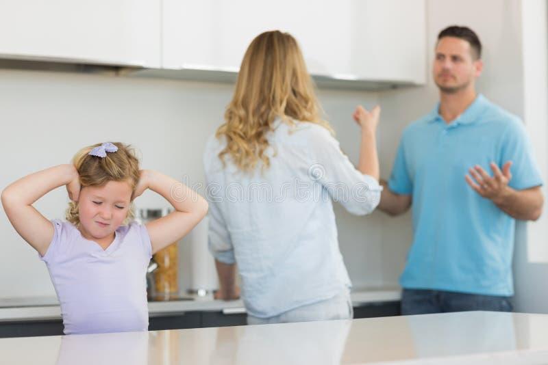 Oídos de la cubierta de la muchacha mientras que discusión de los padres imagen de archivo libre de regalías