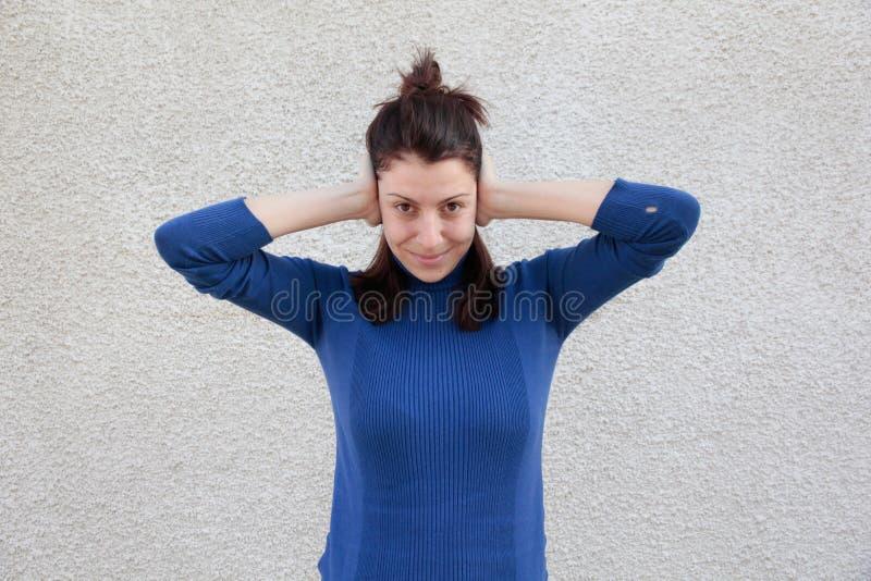 Oídos de la cubierta de la mujer joven con las manos imagenes de archivo