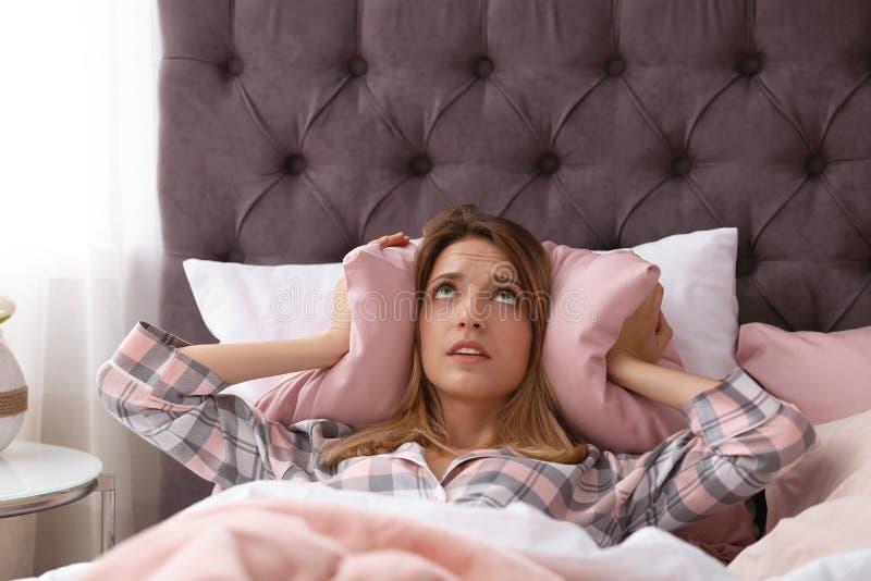 Oídos de la cubierta de la mujer joven con la almohada mientras que intenta dormir en cama en casa imagenes de archivo