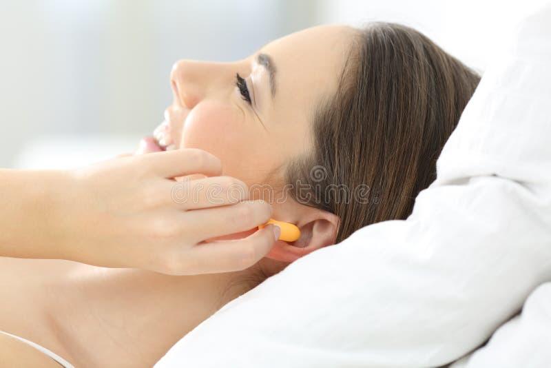 Oídos de la cubierta de la mujer usando los enchufes en la cama foto de archivo