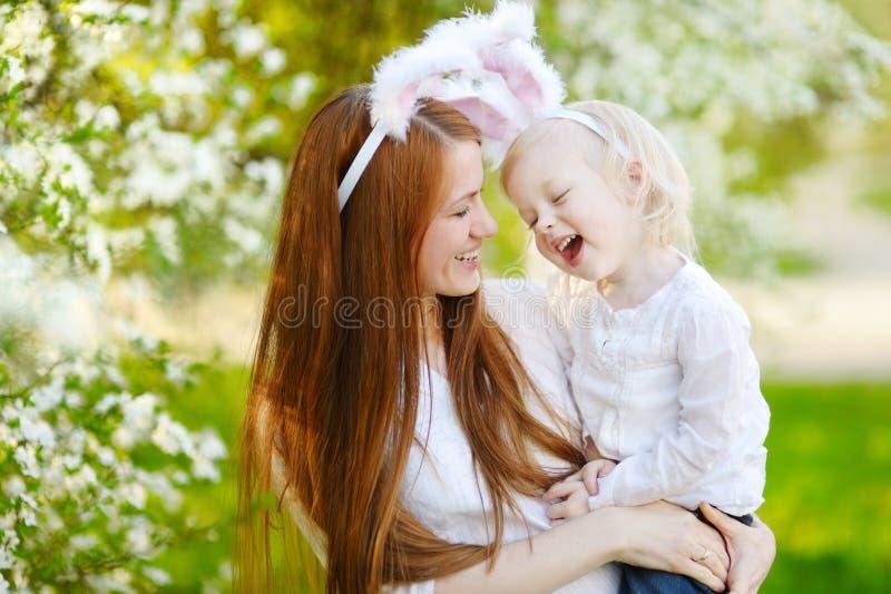 Oídos del conejito de la madre que llevan y de la hija en Pascua imágenes de archivo libres de regalías