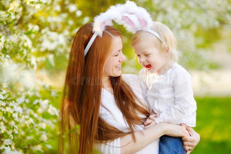 Oídos del conejito de la madre que llevan y de la hija en Pascua foto de archivo