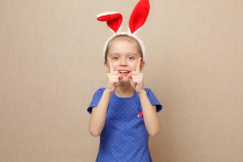 Oídos del conejito de la muchacha del pequeño niño que llevan el día de Pascua foto de archivo
