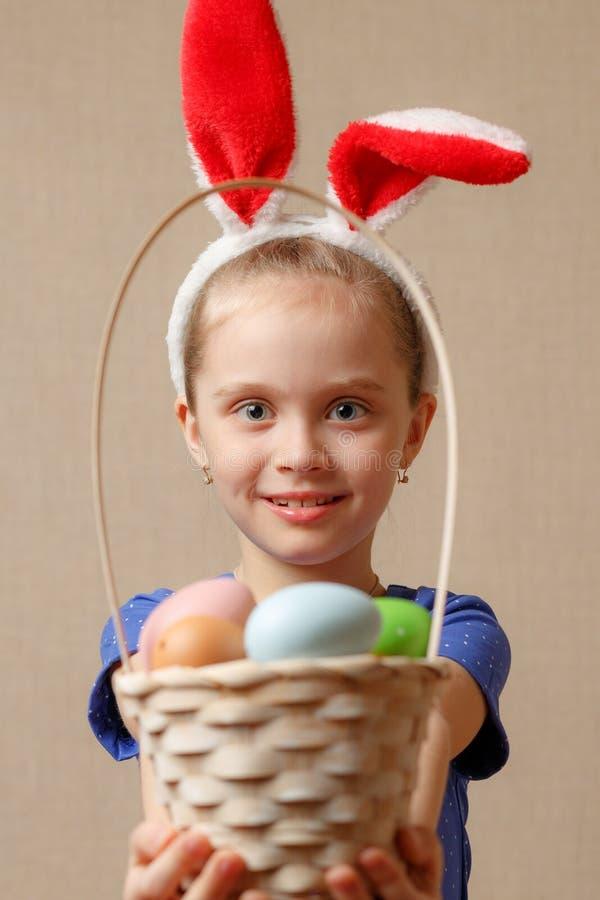 oídos del conejito de la niña que llevan que sostienen una cesta con los huevos de Pascua imagen de archivo libre de regalías